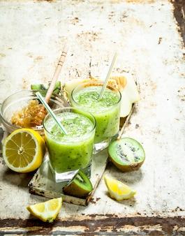キウイ、メロン、レモンのグリーンスムージーとハチミツ。素朴な背景に。