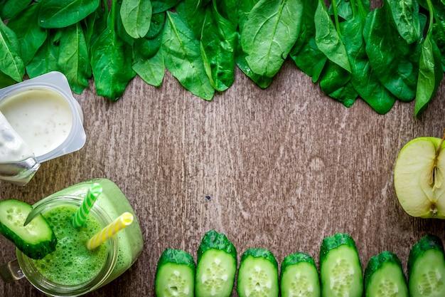 나무 배경에 사과, 요구르트, 시금치, 오이를 넣은 녹색 스무디. 텍스트를 위한 장소가 있는 평평한 위치. 완전 채식 및 건강 식품 개념
