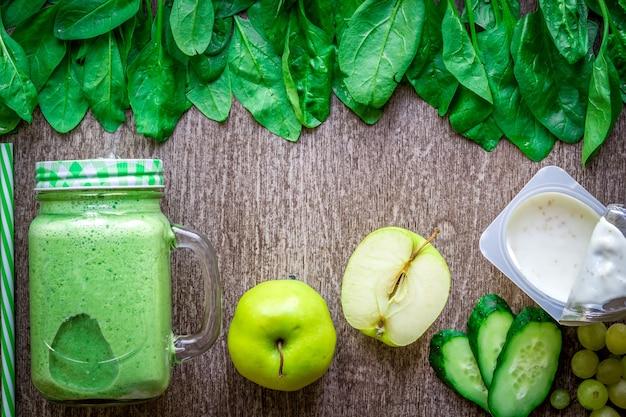 나무 배경에 사과 요구르트 시금치 오이를 넣은 녹색 스무디