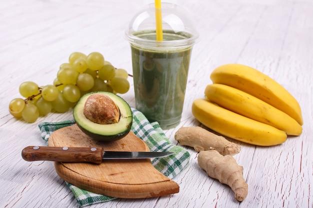 Зеленый коктейль с бананами, лаймом, виноградом и авокадо лежат на столе