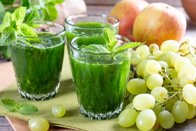 Зеленый коктейль со здоровыми фруктами и овощами на деревянном столе. концепция здорового питания