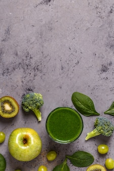 Green smoothie with ingredients on concrete surface