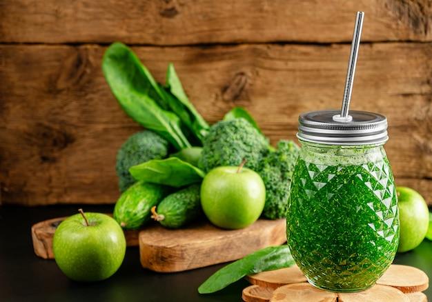 木製の壁に食材を使った緑のスムージー。