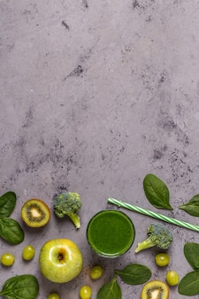 Green smoothie with ingredients, top view, copy space