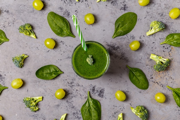 Green smoothie with ingredients, top view