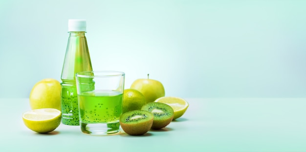 Green smoothie with organic ingredients and fruits on a modern kitchen table. copy space banner.