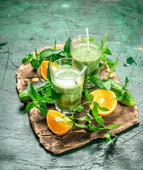 Green smoothie with vegetables, fruits and mint. on rustic background.