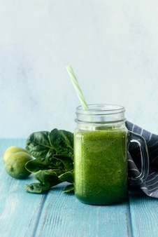 Green smoothie on wooden table