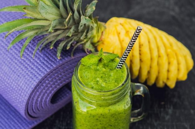 Зеленые коктейли из шпината и ананаса и коврик для йоги. концепция здорового питания и спорта.
