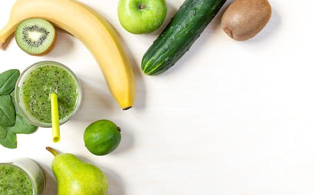 テーブルの上のほうれん草、キウイ、その他の果物や野菜の緑のスムージー。フラットレイ、コピースペース。