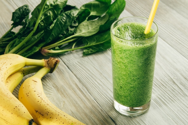 Green smoothies of spinach and banana in a glass with yellow straw on white wood
