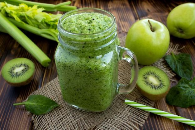 素朴な木製の果物と野菜と緑のスムージー