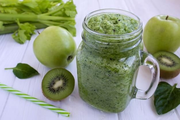 白い木製の背景に果物や野菜と緑のスムージー
