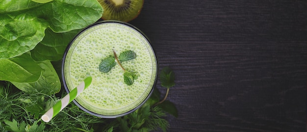 Green smoothies with spinach, cucumber and parsley in a glass on a black background