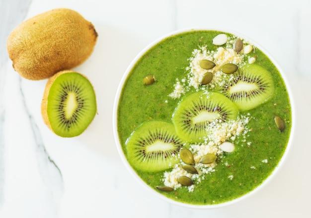 흰색 바탕에 키비와 견과류로 장식된 녹색 스모디. 평평한 평지, 평면도
