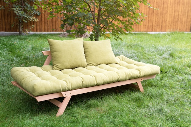 Green sofa in the yard outdoors. outdoor furniture in green garden patio.