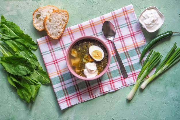 ボウルに緑のスープ。卵と葉、玉ねぎ、緑のテーブルの上のパンとスイバスープ