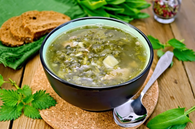 木の板にスイバ、イラクサ、ほうれん草のボウル、スプーン、パン、コショウの緑のスープ
