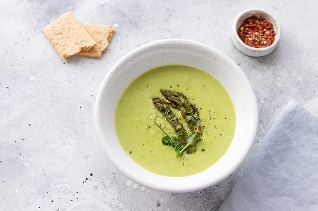 アスパラガスとココナッツミルクの健康的なビーガンフードのコンセプトと緑のスープ