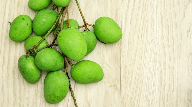 Green sour mango (raw mango) on a wooden table.
