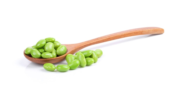 Green soy beans in wood spoon on white