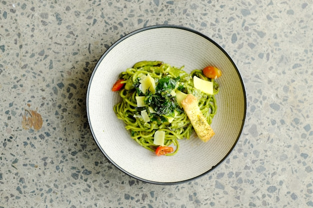 Green spaghetti with cheese and tomato on the plate