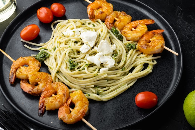 페스토 소스와 구운 새우 꼬치 세트, 접시에, 블랙에 그린 스파게티