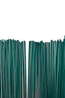 白い背景の上のスピルリナと緑のスパゲッティ。有機由来の天然食用色素を使用したカラーパスタ。