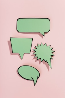 Green speech bubbles with black border on pink background