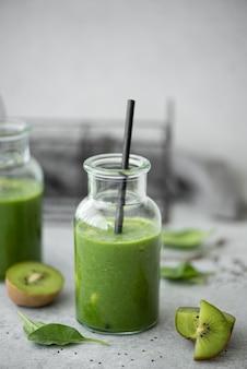 緑のほうれん草、バナナ、キウイのスムージーとチアシードと灰色のテーブルの上の小さなボトル