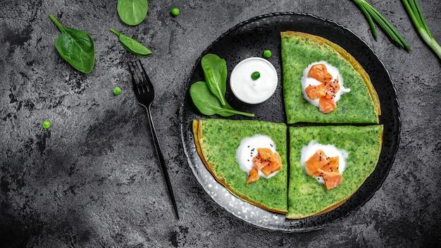 スモークサーモンとサワークリームを添えたグリーンほうれん草のクレープまたはパンケーキ。バナー、メニュー、レシピ、テキストの場所。