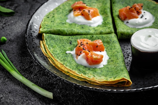 黒いプレート、暗い背景、食品レシピの背景にスモークサーモンとサワークリームと緑のほうれん草のクレープまたはパンケーキ。閉じる。