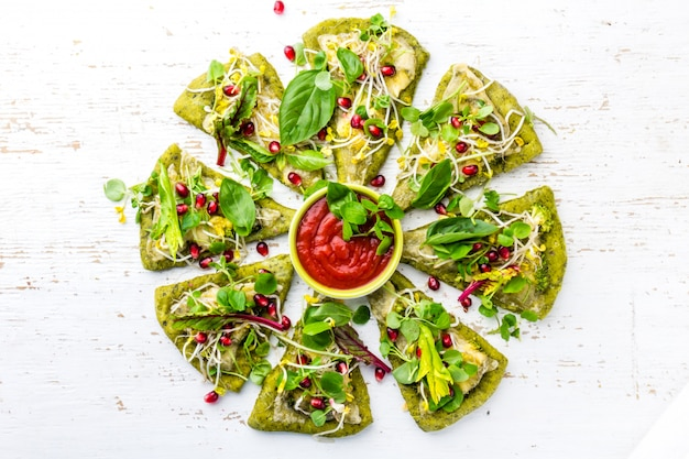 Green spinach dough with vegetables and cheese pizza on wite background