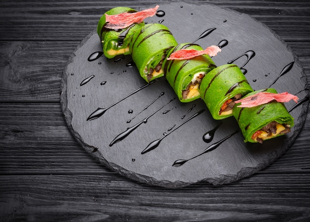 Green spinach pancakes stuffed with stewed meat and cheese on wooden background