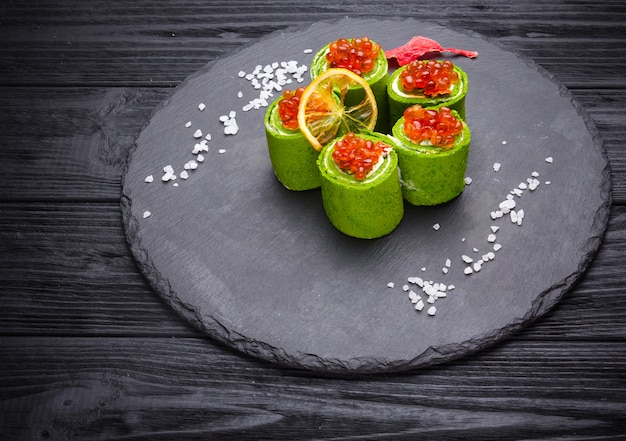 Green spinach pancakes with red caviar and cream cheese on wooden background