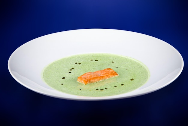 Green spinach puree soup with salmon slices. flat lay top view on a white plate on a blue background.