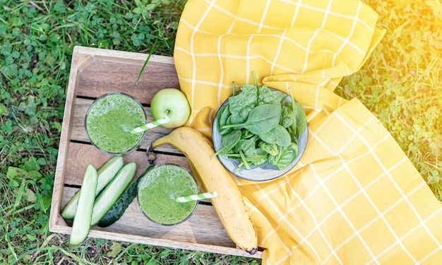 Green spinach smoothies with fruits, banana, apple, cucumber