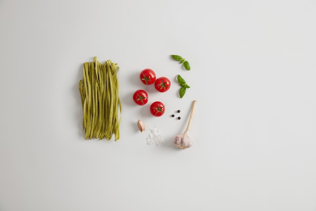 緑のほうれん草のタリアテッレパスタと新鮮な食材は、白い背景で隔離されます。おいしい夕食の準備。有機製品と食品。バランスの取れた食事。イタリアのグルメ料理。ローフードの組成