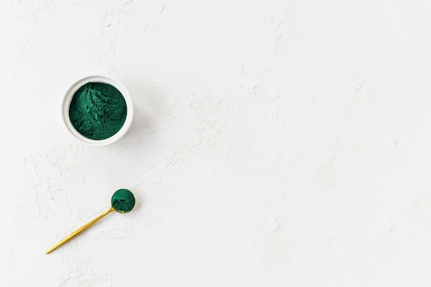 Green spirulina powder in a spoon and bowl with copy space