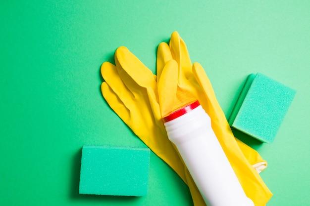 クリーニング用の緑色のスポンジ、黄色のゴム手袋、粉末洗剤用の白いペットボトル