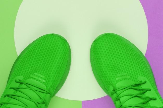분홍색 파스텔 원이 있는 색 배경에 녹색 스포츠 운동화. 청소년 힙스터 개념입니다. 평면도