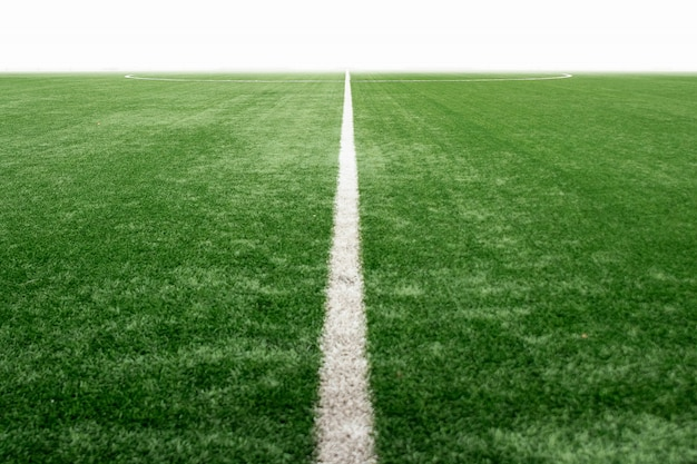 Green sports field with artificial grass, football field perspective.