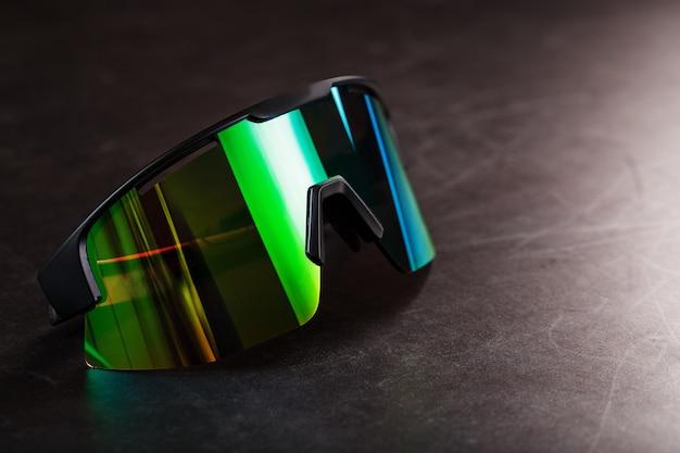 어두운 표면에 미러 렌즈가 달린 녹색 스포츠 안경