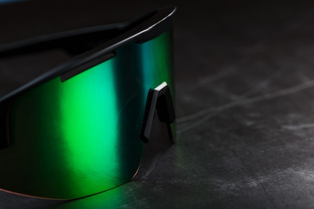Green sports glasses with a mirror lens on a dark surface