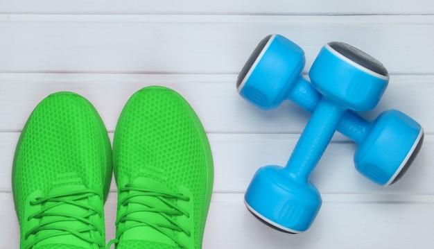 Зеленая спортивная обувь для тренировок, гантели на белом деревянном полу. вид сверху.