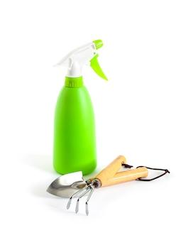 흰색 바탕에 녹색 스프레이 병 및 정원 도구. 식물 관리 개념입니다.