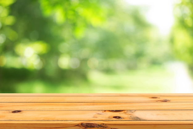 Green spring background with wooden table in summer