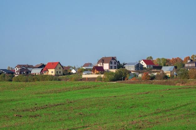 澄んだ青い空を背景に丘の上にあるモダンな村の前にある緑の春の野原。