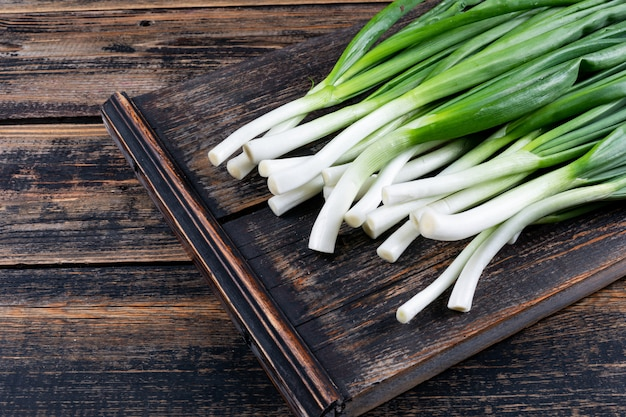 Green spring onions or scallions on a cutting board on a dark wooden table