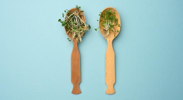 Зеленые ростки чиа, рукколы и горчицы в деревянной ложке на синей поверхности, вид сверху. полезная добавка к пище, содержащая витамины с, е и к.